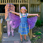 St Mary's childcare centre children in dress-up costumes outside our playhouse.
